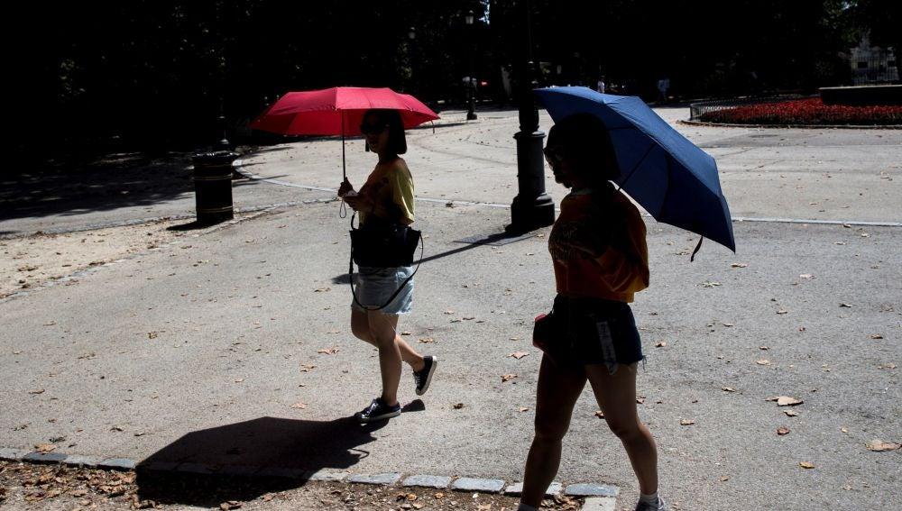 Turistas protegiéndose del calor