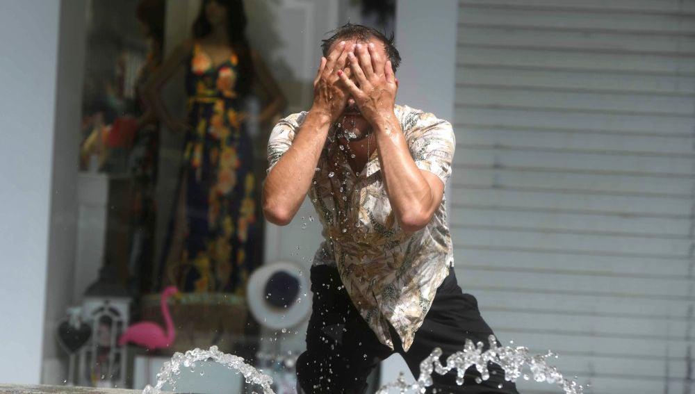 Un hombre intenta refrescarse en una fuente de Córdoba, en una jornada marcada por la ola de calor que afecta a toda la Península
