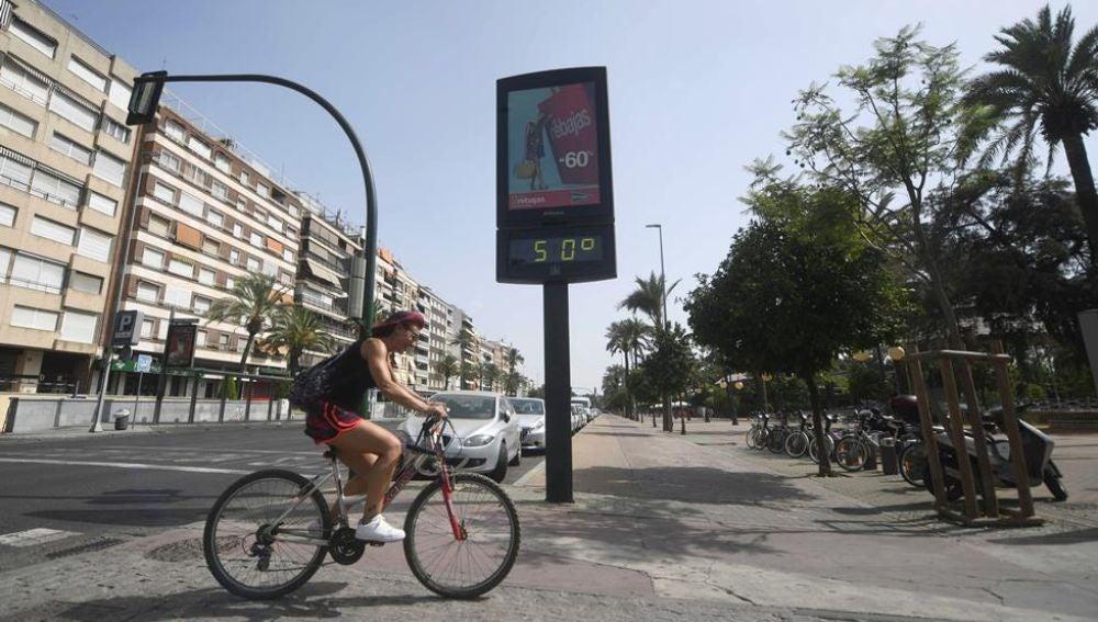 Un ciclista pasa junto a un termómetro que marca 50 grados en Córdoba, en una jornada marcada por la ola de calor que afecta a toda la Península