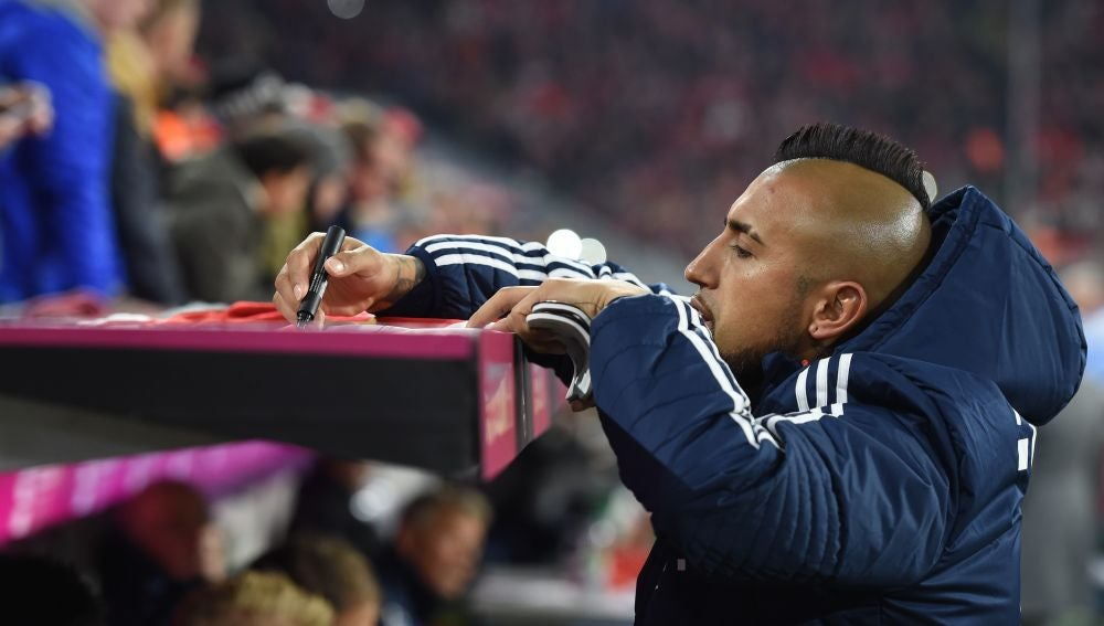 Arturo Vidal firma la camiseta de un aficionado en un partido del Bayern