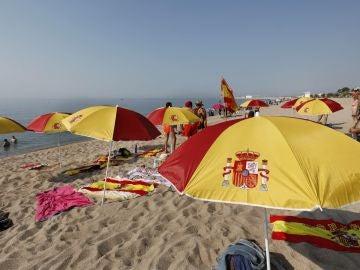 Una quincena de personas ha plantado una decena de sombrillas con los colores de la bandera de España.