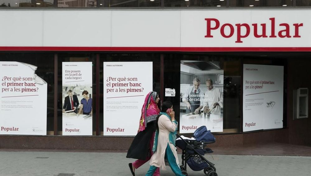 Unas mujeres pasan ante una oficina del Banco Popular.