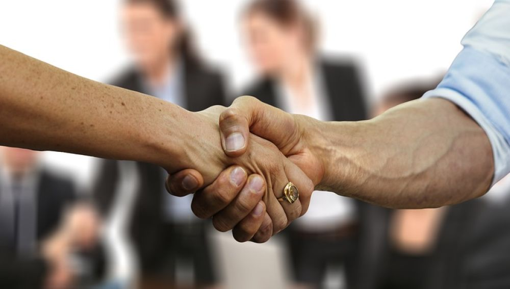 Un hombre y una mujer se dan la mano