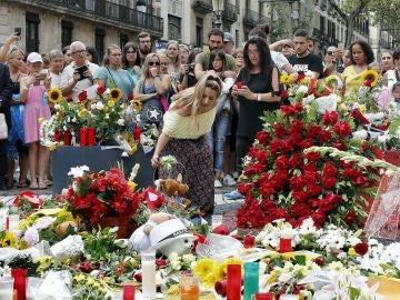 Grupo de personas depositan flores esta tarde en el mosaico de Miró en Las Ramblas