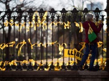 Una mujer coloca lazos amarillos en la verja del Pac de la Ciutadella
