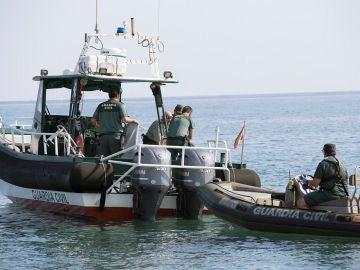 Agentes del Servicio Especial de Actividades Subacuáticas de la Guardia Civil tras recuperar el cadáver de un joven en una playa de Salobreña
