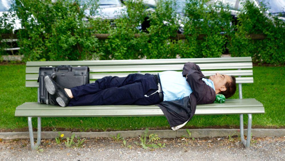 Hombre tumbado en un banco