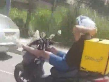 Con las manos detrás de la cabeza y las piernas sobre el manillar: la temeraria acción de un repartidor mientras otro hombre le graba