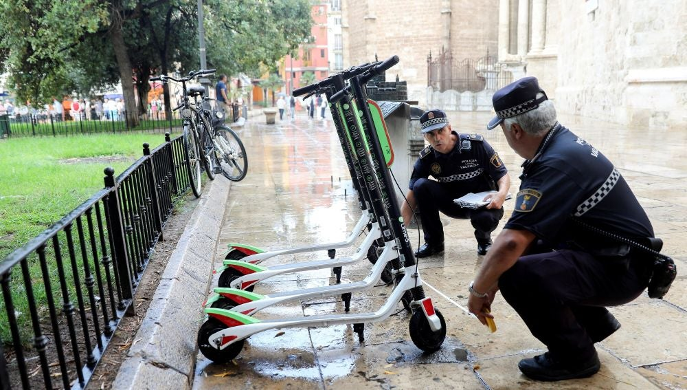 Unos agentes de la Policía Local trabajan en la retirada de los patinetes