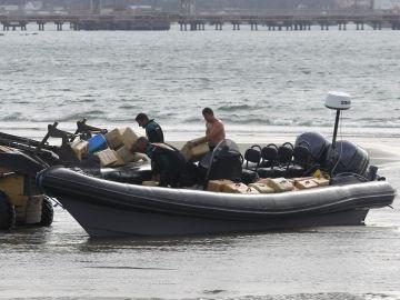 Agentes de la Guardia Civil trasladan los fardos de hachís incautados en una embarcación de tipo neumática en Cádiz