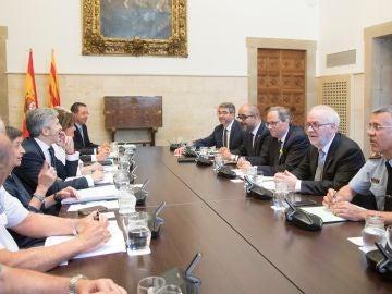 El presidente de la Generalitat , Quim Torra (3d), junto al conseller de Interior Miquel Buch (2i) en la parte derecha de la mesa junto al ministro de Interior, Fernando Grande-Marlaska