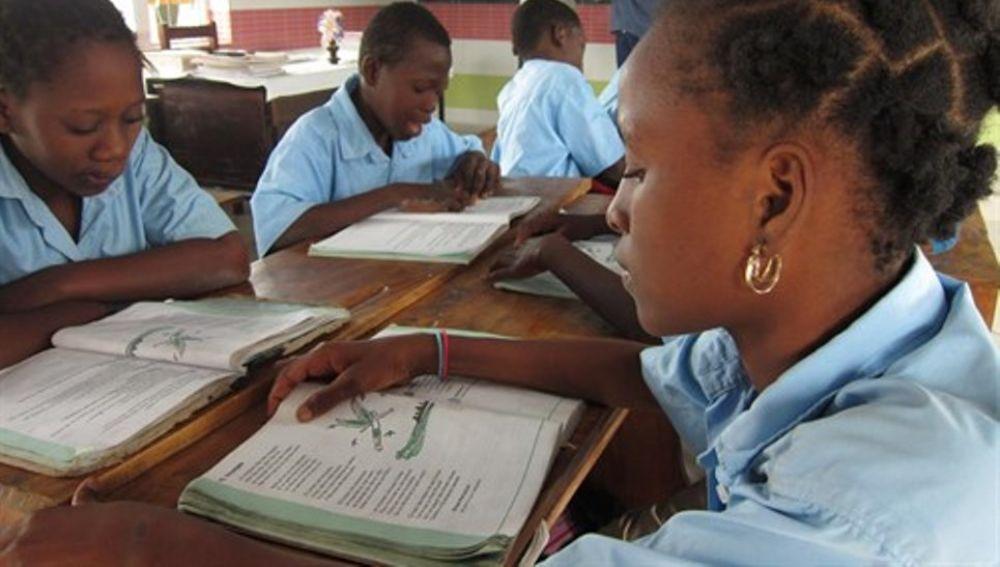 Niños leyendo un libro de texto en una escuela