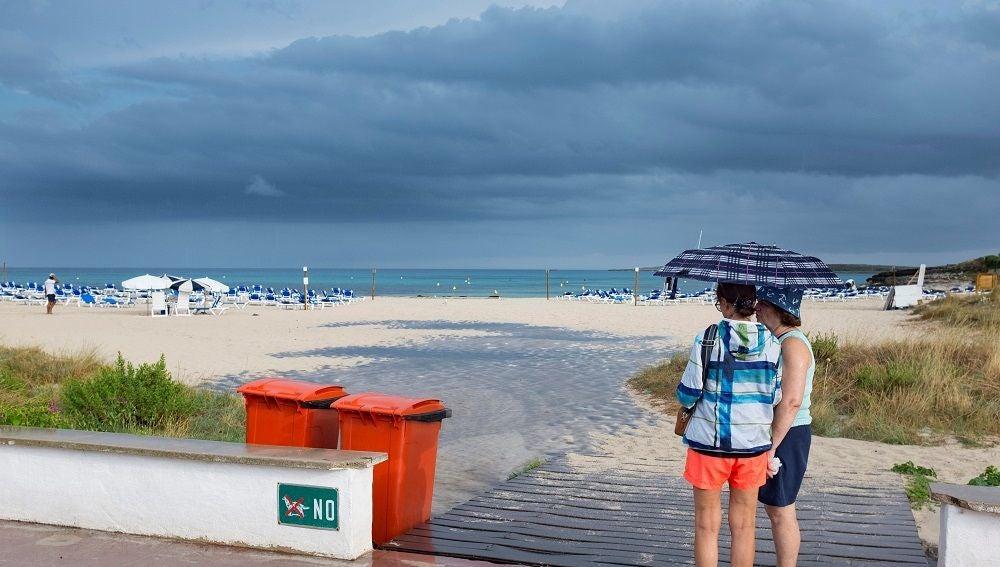 Dos mujeres se resguardan de la lluvia bajo un paraguas en una playa de Menorca