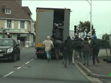 Decenas de migrantes tratan de subir a un camión para alcanzar Reino Unido
