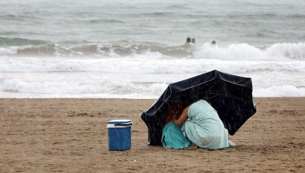 Una mujer se protege de la lluvia con su sombrilla en la playa de la Malvarrosa bajo la lluvia