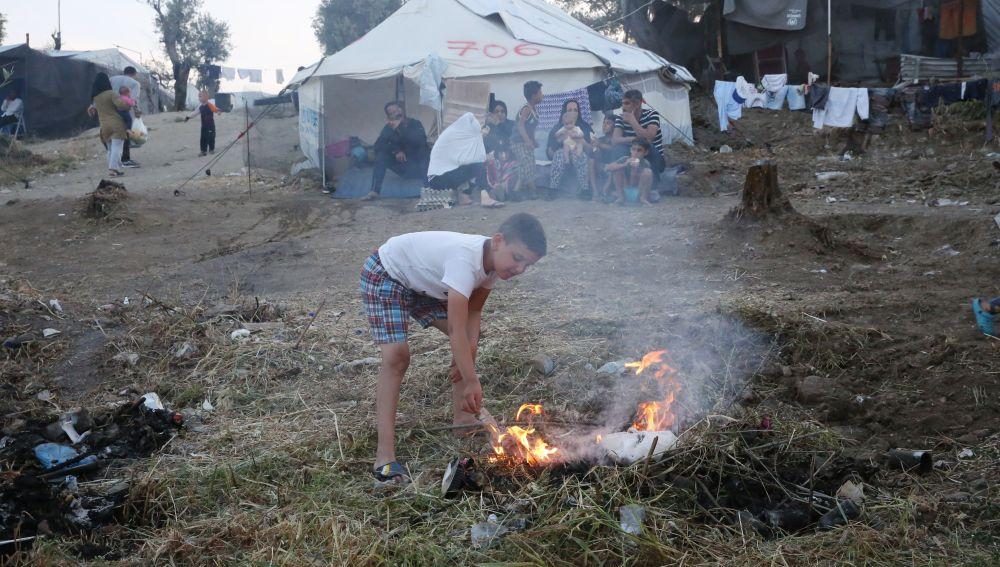 Un niño hace un fuego en el campamento de refugiados de Moria, en la isla de Lesbos (Grecia)