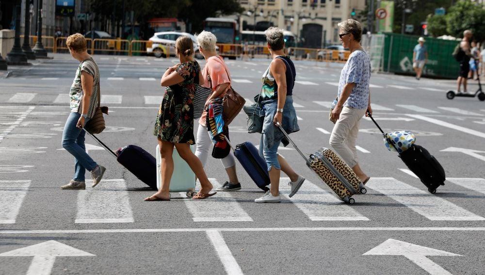 varias turistas arrastran sus maletas tras abandonar un hotel