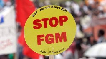 """Una mujer levanta una pancarta en la que dice """"Poned fin a la mutilación genital femenina (FGM)' durante una gran manifestación, desde Kibera, el mayor barrio marginal de Africa en Nairobi, Kenia"""