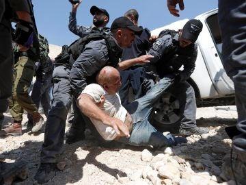 Soldados israelíes detienen a un palestino mientras los manifestantes bloquean el paso a una excavadora del ejército israelí