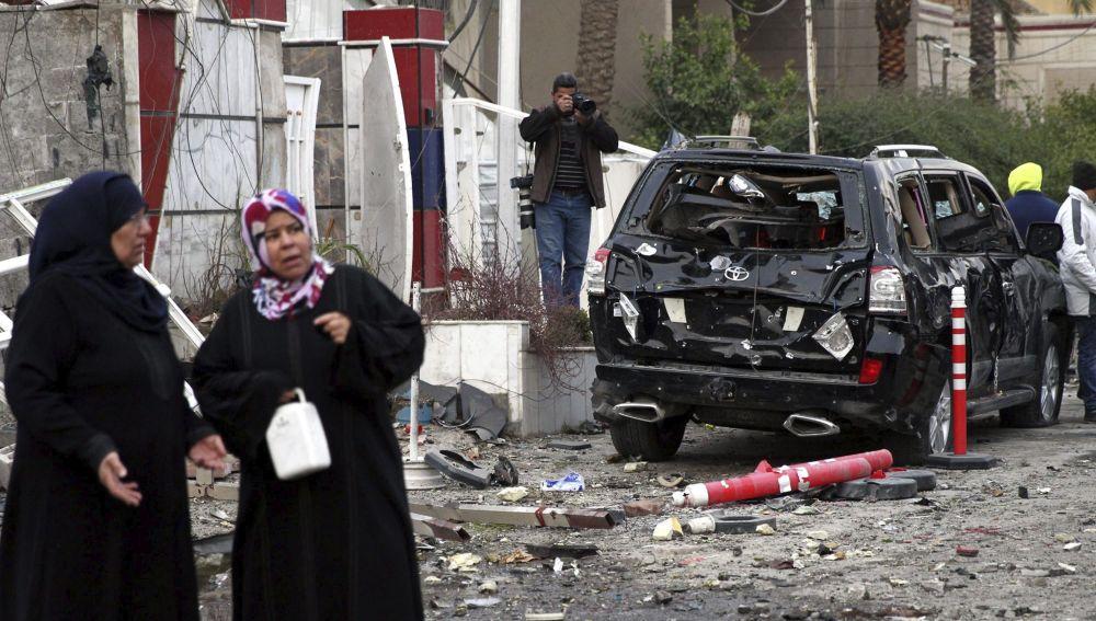 Un grupo de personas permanece en el lugar donde explotó un coche bomba, en Bagdad, Irak