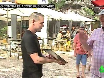 Un camarero aborda a un viandante en la calle
