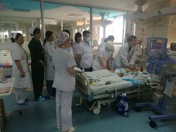 Imagen de los médicos chinos junto a la cama del niño
