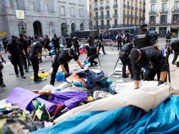"""Los Mossos d'Esquadra procediendo a retirar las tiendas de campaña instaladas desde el pasado 11 de septiembre en la plaza de Sant Jaume de Barcelona por un grupo de independentistas que reclaman que """"se haga efectiva la república catalana"""""""