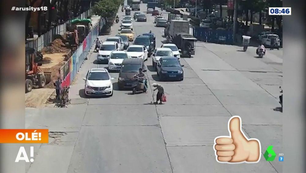 Un motorista para el tráfico para que una señora pueda cruzar la calle