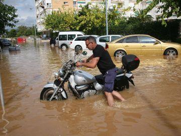 Un vecino intenta mover una motocicleta en el barrio de la Pineda de Vila-Seca (Tarragona)