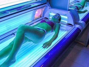 Una joven se somete a una sesión en una cabina de bronceado