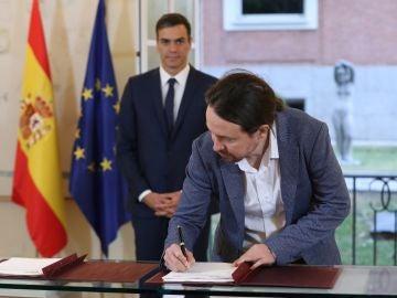 El secretario general de Podemos, Pablo Iglesias, firmando el acuerdo presupuestario