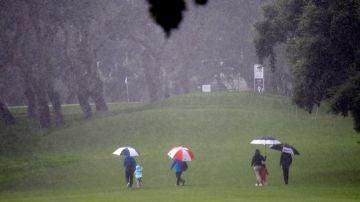 Espectadores cruzan bajo la fuerte lluvia uno de los hoyos del campo del Real Club
