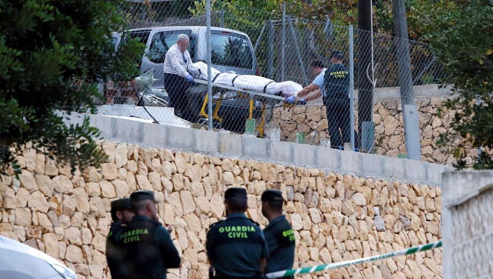 Miembros de los servicios funerarios trasladan uno de los cuerpos