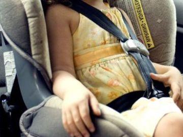 Imagen de archivo de una niña en una sillita en un coche