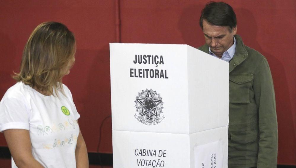 El candidato ultraderechista Jair Bolsonaro, acompañado de su esposa, Michelle, vota en una área militar en la zona norte de Río de Janeiro