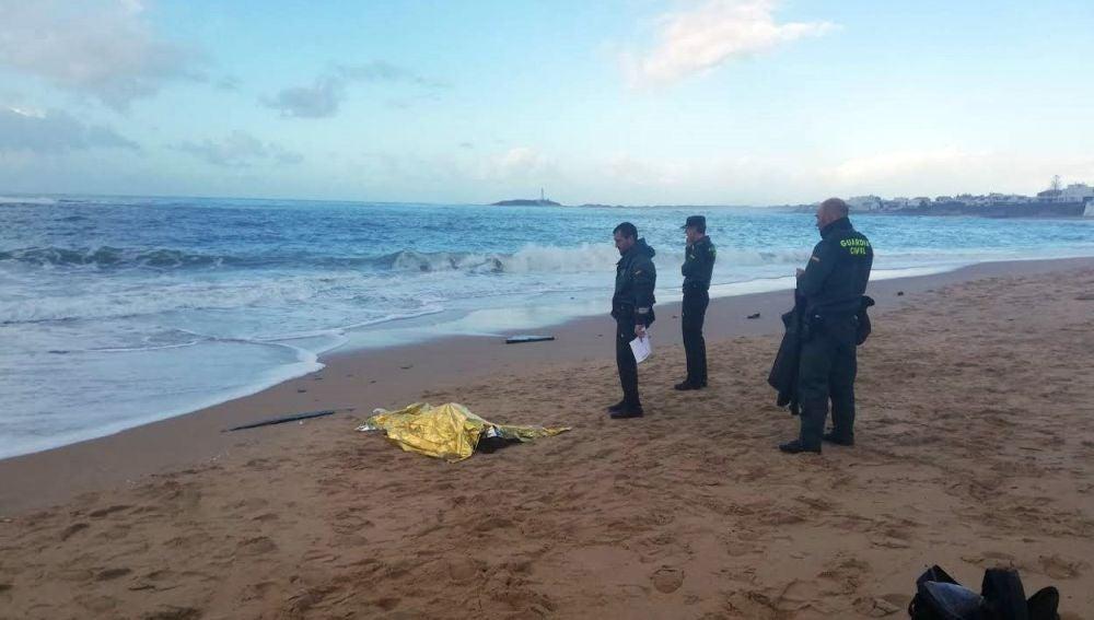Fotografía facilitada por la Guardia Civil que muestra a agentes junto al cuerpo de uno de los inmigrantes fallecidos en la costa de Melilla