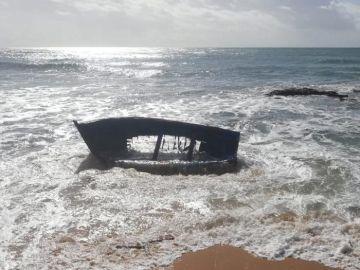 Estado en el que quedó una patera tras chocar contra una roca en la playa de Caños de Meca