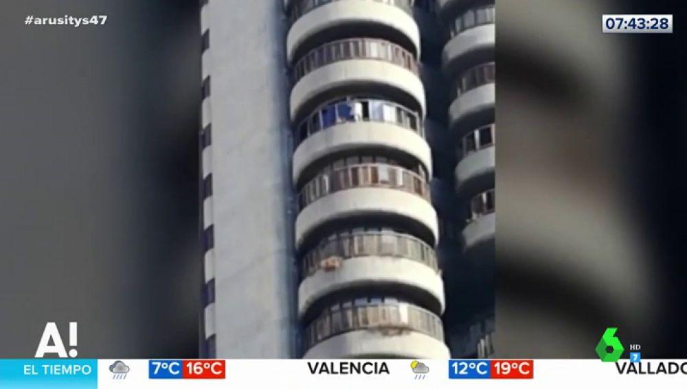 Las impactantes imágenes de una mujer que se juega la vida limpiando ventanas en el edificio Torres Blancas de Madrid