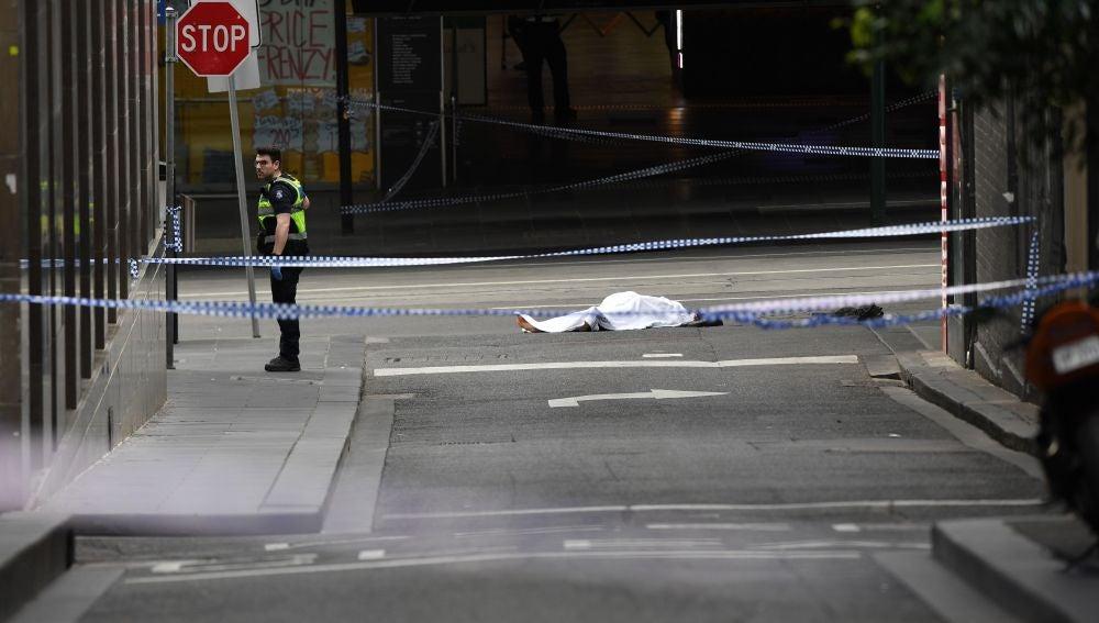 El cadáver de una víctima yace sobre el asfalto