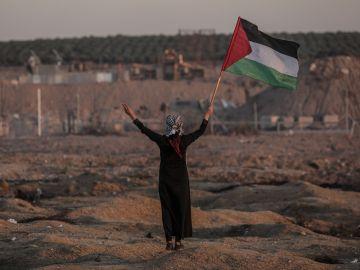 Una mujer ondea una bandera de Palestina