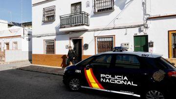 Un agente de la Policía Nacional sale de la vivienda de Alcalá de Guadaira