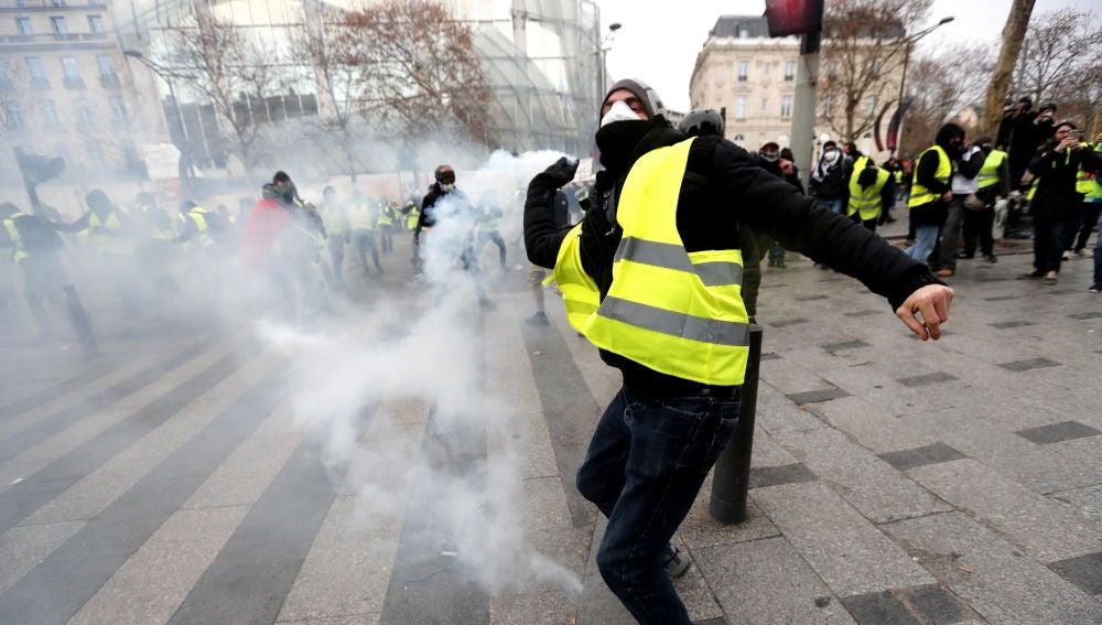 Un manifestante de los 'chalecos amarillos' lanza gas lacrimogeno