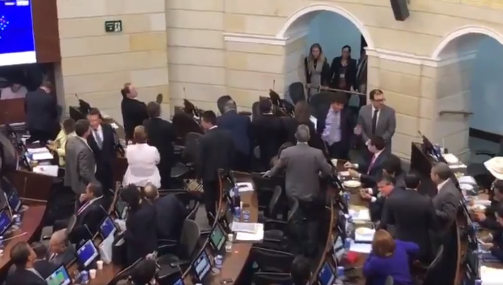 Diputados de Centro Democrático se levantan de sus asientos en el pleno del Congreso colombiano.