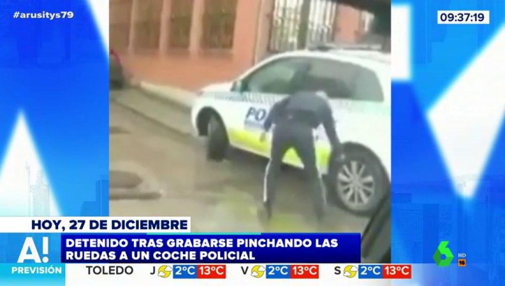 Un joven pincha las ruedas de un coche de Policía