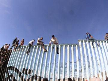 Migrantes saltando la valla fronteriza de EEUU