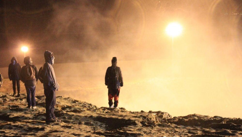 Migrantes esquivan el humo del gas lanzado por los guardias de la Policía fronteriza.