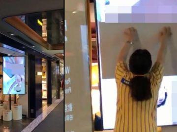Una dependienta trata de tapar la pantalla de un escaparate de Ikea.