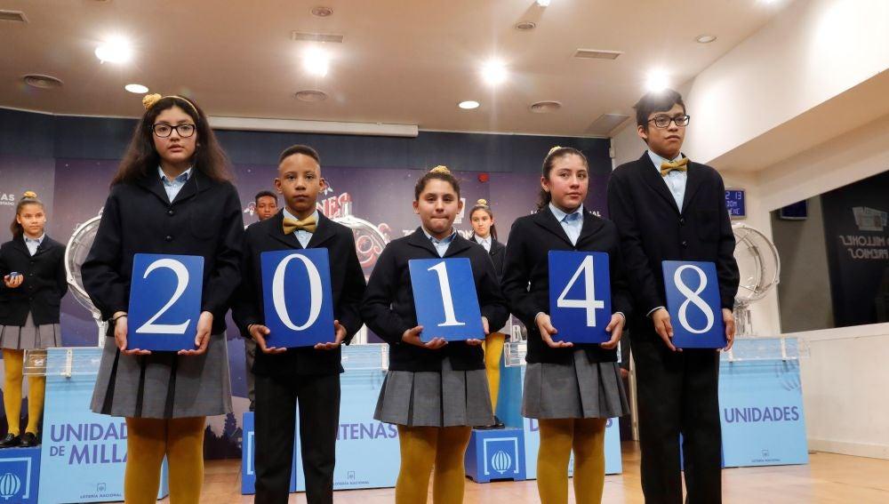 Los niños de San Ildefonso muestran el 20148, agraciado con el tercer premio del sorteo del Niño