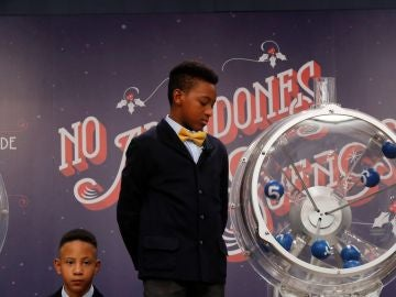 Uno de los niños de San Ildefonso junto al bombo ya preparado para el sorteo de la lotería de El Niño