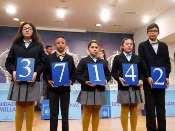 Los niños de San Ildefonso muestran el 37.142, primer premio del sorteo del Niño